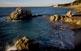 Des de la platja de la roca Grossa de Calella es veu una part de la costa de Sant Pol, presidida per l'absis de l'ermita de Sant Pau.