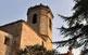 El campanar de l'església de Torà, un temple curiosament aferrat a les cases del poble.