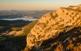 A la sortida del sol, les crestes del Montsec d'Ares es tenyeixen de roig. Al fons hi ha, cobert de boires matineres, l'embassament de Canelles.