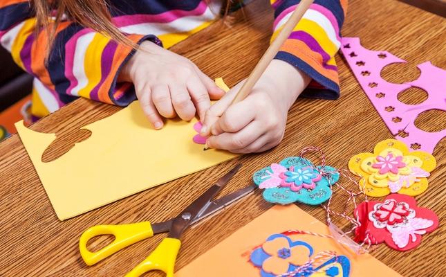 Una nena dibuixa les flors per fer la decoració