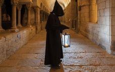 El monjo que guia la visita nocturna pel monestir de Sant Cugat