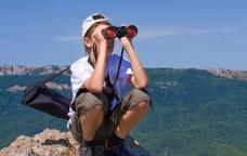 Un noi observa amb uns prismàtics