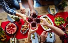 Taula amb menjar i brindis amb vi