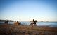 A lloms d'un cavall per la platja de...